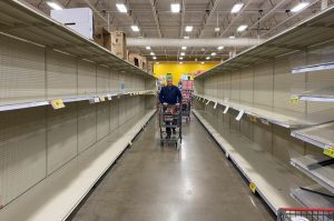Grocery store aisle with empty shelves